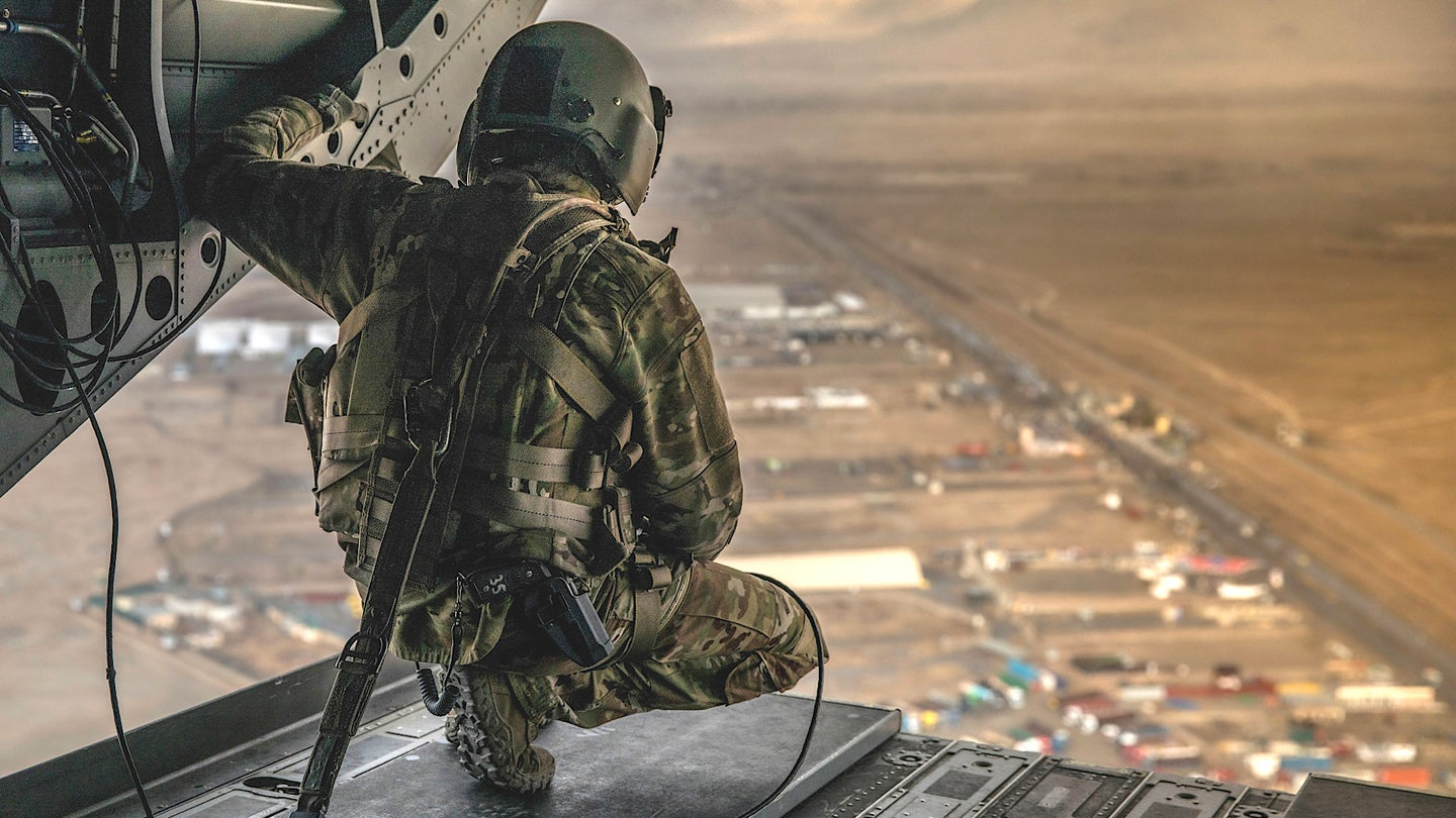 A member of the US Army's 10th Mountain Division looks out of the back of a CH-47 Chinook helicopter in Afghanistan.